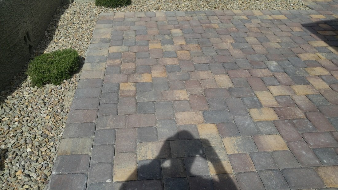 A shadow across an outdoor area with paver wet sealing